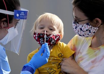 One-year-old Quentin Brown, is held by his mother, Heather Brown, as he eyes a swab while being tested for COVID-19 at a new walk-up testing site at Chief Sealth High School, Friday, Aug. 28, 2020, in Seattle. The child's daycare facility requires testing for the virus. The coronavirus testing site is the fourth now open by the city and is free. (AP Photo/Elaine Thompson)