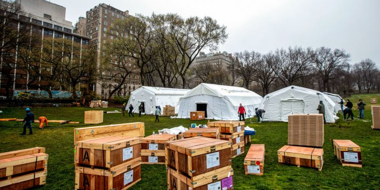 A Samaritan's Purse crew works on building an emergency field hospital equipped with a respiratory unit in New York's Central Park across from the Mount Sinai Hospital, Sunday, March 29, 2020. (AP Photo/Mary Altaffer)
