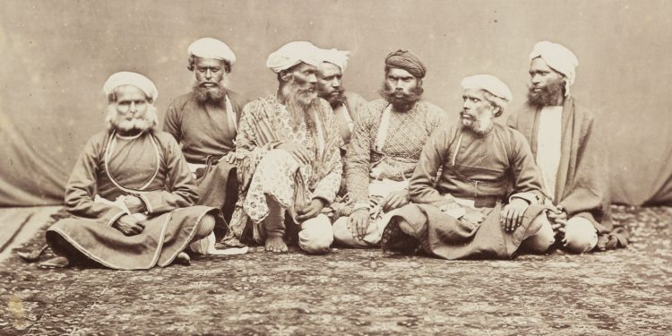 """A photograph of a group of elderly men sitting on a mat, taken in Peshawar, now in Pakistan, circa 1865. Two of the men are looking at each other with contempt, suggesting that they may actually be enemies who have been persuaded to be photographed together as examples of native """"thugs."""""""