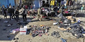 People and security forces gather at the site of a deadly bomb attack in a market selling used clothes, Iraq, Thursday, Jan. 21, 2021. Twin suicide bombings hit Iraq's capital Thursday killing and wounding civilians, police and state TV said. (AP Photo/Hadi Mizban)