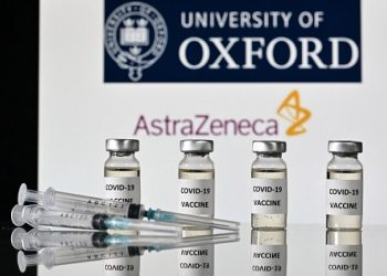 An illustration picture shows vials with Covid-19 Vaccine stickers attached and syringes, with the logo of the University of Oxford and its partner British pharmaceutical company AstraZeneca, on November 17, 2020. (Photo by JUSTIN TALLIS / AFP)